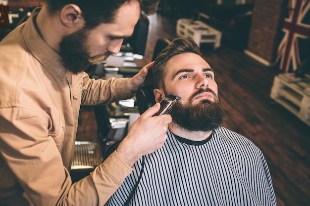 Хороший и хороший парикмахер подстригает часть бороды клиента электрическим бритвой. он делает это очень точно. Premium Фотографии