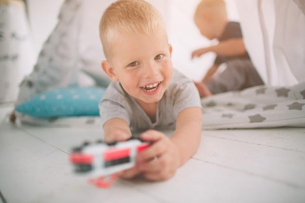 Дети братьев лежат на полу. по утрам мальчики играют дома с игрушечными машинками. повседневный образ жизни в спальне. Premium Фотографии