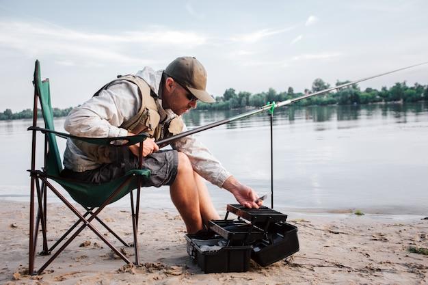 Рыбак сидит в раскладном кресле и наклоняется вперед к раскрытой черной пластиковой коробке. парень держит в руках удочку и пластиковую приманку. на улице становится холодно. Premium Фотографии