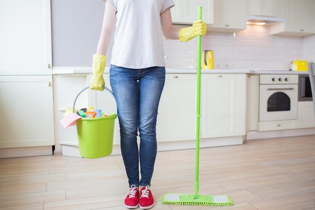 女性のビューをカットキッチンに立って、片方の手でモップでスティックを保持し、もう一方の手で洗浄装置でバケツを保持します。女の子は黄色の手袋を着用しています。 Premium写真