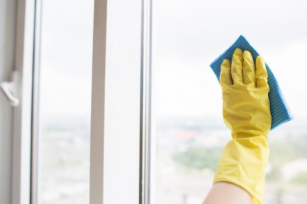 窓のガラスを掃除する黄色い手袋で人間の手。青い布でこれを行います。外の日です。 Premium写真