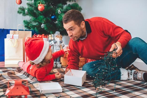 メリークリスマス、そしてハッピーニューイヤー。毛布の上に親子の素敵な写真。女の子は胃に横たわっています。男は子供を見て、クリスマスライトを保持します。彼らは一緒に座っています。 Premium写真