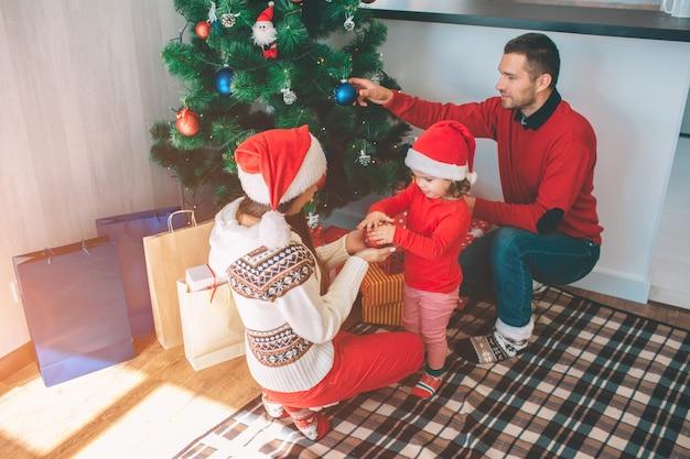 メリークリスマス、そしてハッピーニューイヤー。キュートで素敵な家族の魅力的な写真。彼らはクリスマスツリーを飾る。若い女性は、小さな女の子とおもちゃを保持しています。男は木に青いおもちゃを置きます。 Premium写真