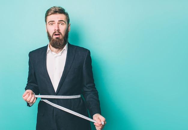 驚いた男が立って、測定テープで自分自身を測定 Premium写真