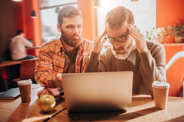 Один из парней расстроен и смотрит на экран ноутбука, а другой с надеждой и грустью смотрит на своего друга. Premium Фотографии