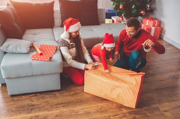 メリークリスマス、そしてハッピーニューイヤー。ギフト用の紙を保持している小さなヘルパーの写真。彼女の両親は微笑む。若い男はテープを保持し、プレゼントの表紙に使用します。女性は彼らを助けます。 Premium写真