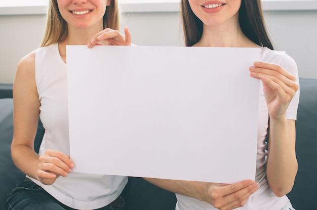 Женщины держат пустую белую бумагу Premium Фотографии