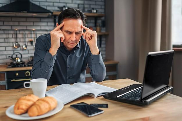 深刻な男は、キッチンと読書のテーブルに座っています。彼は日記を見下ろし、頭を抱えています。男は集中して見える。 Premium写真