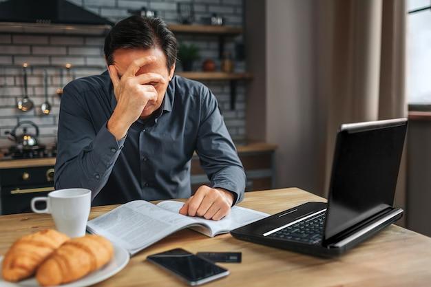 Усталый человек сидеть за столом на кухне. он закрывает лицо рукой. человек работает. у него головная боль. Premium Фотографии