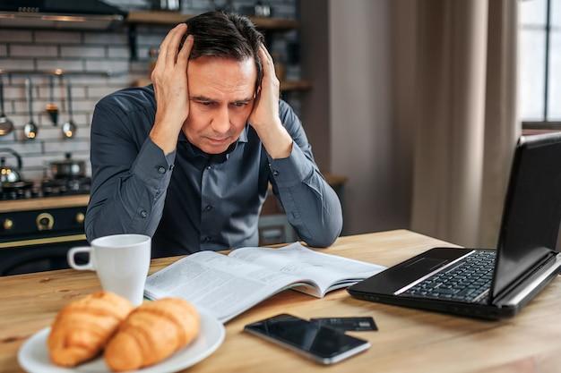 Серьезный концентрированный человек сидеть за столом на кухне. он держится за руки, слышит и читает журнал. человек работает. Premium Фотографии