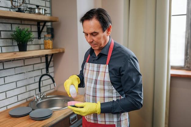 エプロンスタンドに男を集中し、スポンジに洗浄ジェルを注ぐ。彼は見下ろします。男は一人で立つ。 Premium写真