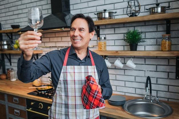 エプロンの素敵な大人の男が一人で立ち、キッチンでガラスを見てください。きれいに輝きます。男はキッチンタオルと笑顔を保持します。 Premium写真