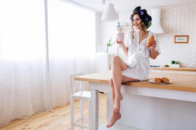 Положительная жизнерадостная молодая женщина на таблице в кухне. беззаботная экономка, держа чашку и круассан в руках. улыбка. одни на кухне. сахарный папа платит за все. Premium Фотографии