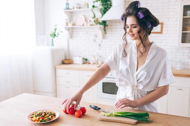Привлекательная славная молодая женщина варя в кухне. встаньте за стол и возьмите нарезанный красный перец. зеленый лук режется на столе. овощи смешать на тарелке. работаю дома. беспечная жизнь. Premium Фотографии