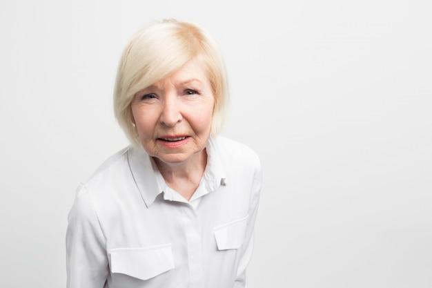 Старая и хитрая женщина очень внимательна к деталям. она пытается проверить все здесь. эта бабушка очень отзывчива и пунктуальна. закройте Premium Фотографии