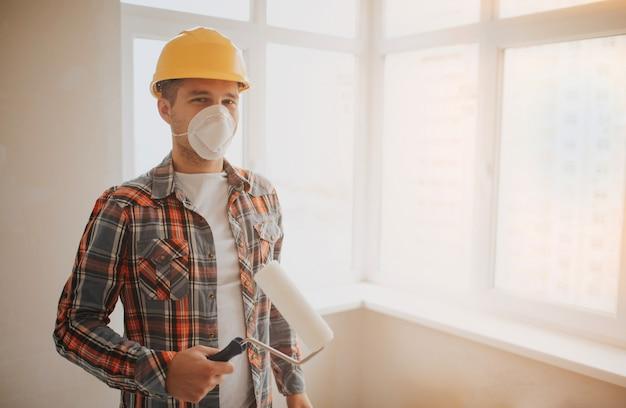 Строитель работает на стройке и измеряет потолок. рабочий в оранжевом шлеме и малярном валике красит стену. Premium Фотографии