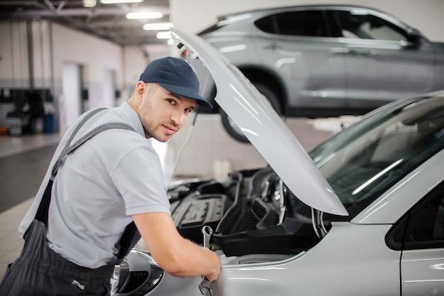 Красивый молодой работник смотрит на камеру. он делает ремонт переднего кузова автомобиля. парень носит кепку и униформу. Premium Фотографии