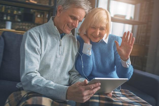 Несколько пожилых людей разговаривают со своими детьми, используя технологии Premium Фотографии