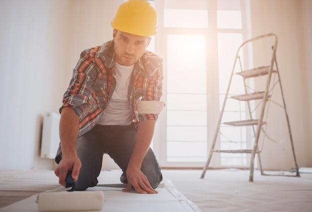 Рабочий прикрепляет обои. строитель наносит клей на обои Premium Фотографии