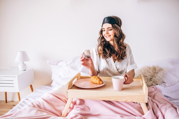 ベッドに座っている黒髪の若い女性とケーキを手に保持します。朝食の朝。寝室に一人で。美しいモデルはピンクのパジャマと黒いフェイスマスクを着用します。 Premium写真