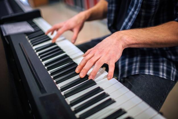 Закройте человека, играющего на клавиатуре. он сидит один в комнате. Premium Фотографии