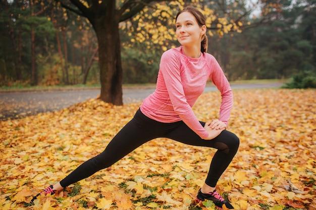 公園の外に伸びる素敵で陽気な若い女性。彼女は側に見えます。女性は片方の膝に手をつないでいます。彼女は一人でポジティブです。 Premium写真
