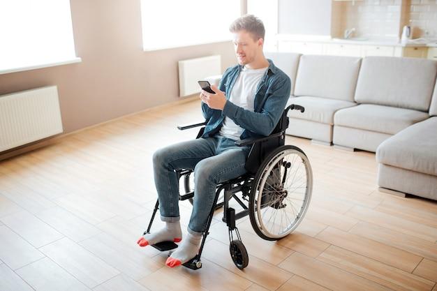 包含と障害を持つ素敵な若い男。車椅子に座っています。電話を手に持って見てください。大きな空の部屋で日光。 Premium写真