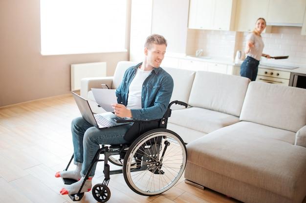 包括性と障害を持つ魅力的な若い学生。椅子に座って振り返る。ストーブで調理する若い女性。お互いに見てください。部屋のカップル。 Premium写真