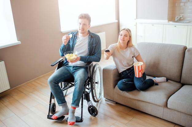 若い男が車椅子に座って、ガールフレンドと映画を見ています。障害と特別なニーズを持つ人。若い女性はソファに座って、食べ物とボウルを保持します。リモコン。 Premium写真