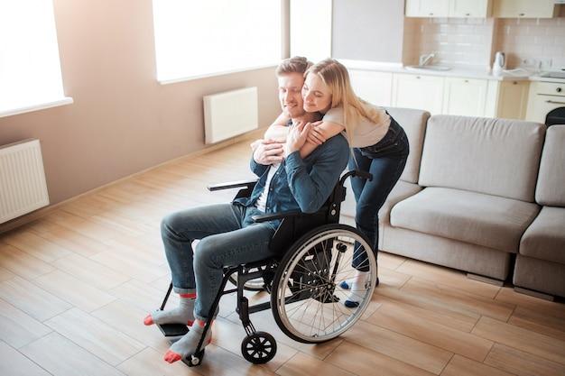 陽気な感情。車椅子に座っている障害を持つ若者。女性は後ろに立って彼を抱きしめます。素敵なカップルは一緒に時間を過ごします。 Premium写真