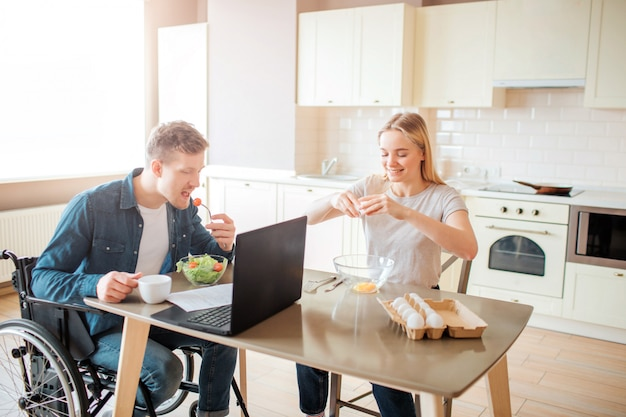 Молодой человек с инклюзивностью и особыми потребностями, едят салат на кухне. сижу на коляске и учусь. молодая женщина сидит рядом и разбивает яйца. работая вместе. Premium Фотографии