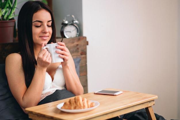 Молодая красивая женщина завтракает на кровати Premium Фотографии