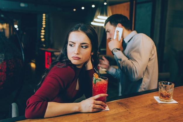 右を見ている少女の悲しい写真。男は電話に応答していて、彼女と時間を過ごしていないので、彼女は悲しいです。彼女は気分がよくありません。 Premium写真