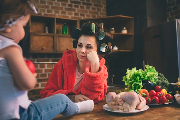自宅で母を強調しました。家庭の台所で小さな子供を持つ若い母親。彼女の赤ちゃんの世話をしながら多くのタスクを行う女性 Premium写真