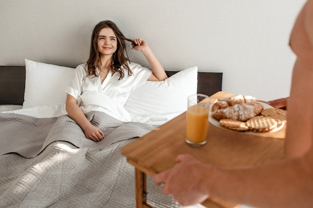 ベッドで若いカップル。幸せな美しい空腹の女性は、朝のロマンチックな朝食を待っています。 Premium写真