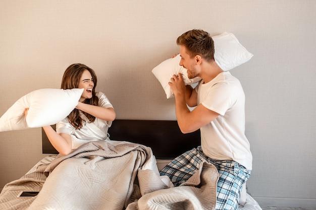 ベッドで若いカップル。パジャマ姿で笑顔の幸せな男と女が浮気し、枕で戦って、おはよう Premium写真