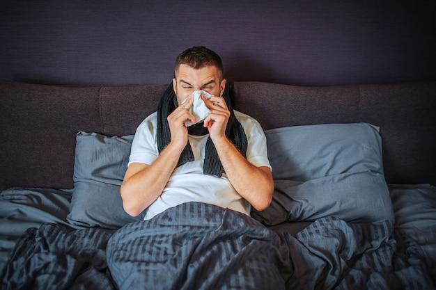 病気の若い男がベッドに座っています。彼は毛布で覆われています。組織にくしゃみをする男。彼は苦しんでいます。若い男はひどい感じです。彼はくしゃみに集中しています。 Premium写真