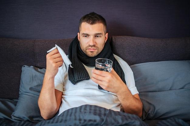 気を取られた若い病人は、体の覆われた低い部分でベッドの上に座っています。彼は水に白いナプキンとグラスを持っています。また、首にスカーフがあります。 Premium写真