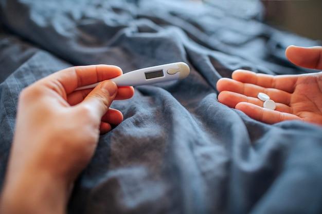 人間が片手で持ち、もう一方の手で丸薬を持つ白い温度計の写真。彼はベッドに座って、紺色の毛布で覆われています。 Premium写真