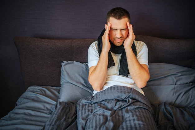 若い男はベッドに座って、額の近くに手を保持しています。彼は頭痛に苦しんでいます。痛みは強くてひどいです。男が縮む。彼は首にスカーフを持っています。 Premium写真
