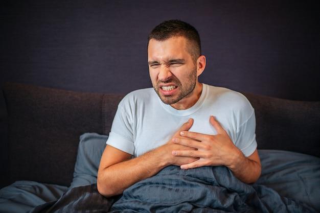 若い男は熱攻撃に苦しんでいます。彼はその場所で手をつないでいます。彼は縮む。若い男はひどい感じです。彼は体の覆われた低い部分でベッドに座っています。 Premium写真