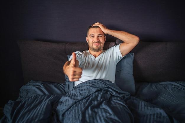 面白い若い男がベッドの上に座って、笑顔します。彼は片方の手に大きな親指を見せ、もう片方の手を頭にかざします。男は満足して幸せです。 Premium写真
