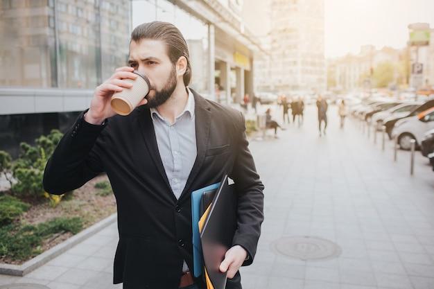 Занятый человек спешит, у него нет времени, он собирается разговаривать по телефону на ходу. бизнесмен делает несколько задач на капоте автомобиля. многозадачный деловой человек пьет кофе Premium Фотографии