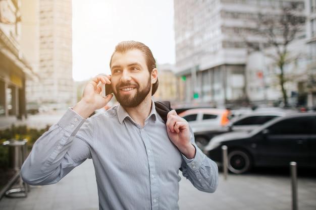 Занятый человек спешит, у него нет времени, он собирается разговаривать по телефону на ходу. бизнесмен делает несколько задач. многозадачность делового человека. Premium Фотографии