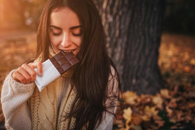 落ちた秋に座って美しい若いブルネットの葉公園 Premium写真