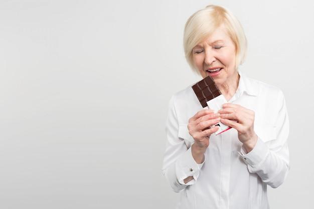 ミルクチョコレートのバーを食べているモートレの女性の写真。彼女はお菓子を食べるのが好きです。彼女は健康を大事にしていますが、今はチョコレートの味を楽しみたいと思っています。 Premium写真