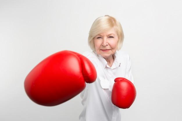 赤いボクシンググローブを身に着けている深刻な女性が位置に立っています。彼女はいくつかの演習を行う準備ができています。 Premium写真