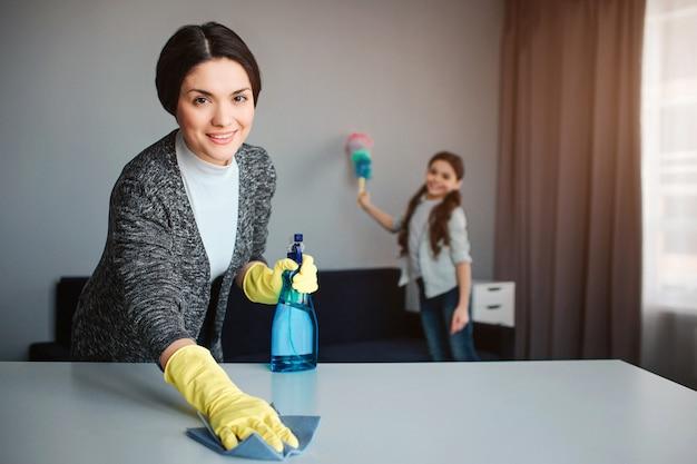美しいブルネットの白人の母と娘が部屋で一緒に掃除します。陽気な若い女性が机を洗うし、スプレーを保持します。女の子は後ろに立ってほこりを吹き飛ばします。 Premium写真