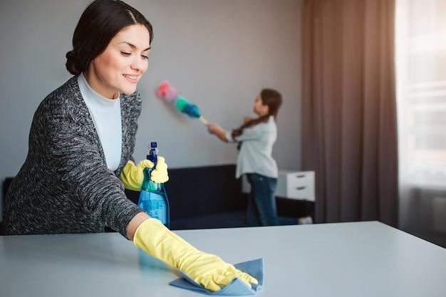 美しいブルネットの白人の母と娘が部屋で一緒に掃除します。龍女洗濯テーブルと笑顔。女の子は後ろに立ってほこりを吹き飛ばします。 Premium写真