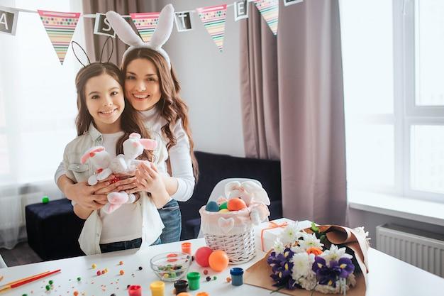 素敵なポジティブな母と娘はエステルの準備をします。彼らはウサギのおもちゃを持ち、カメラに笑顔を浮かべます。母抱擁娘。部屋のテーブルの装飾と絵画。 Premium写真